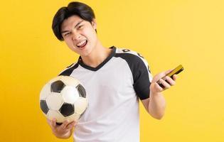 hombre asiático está sosteniendo una pelota y sosteniendo un teléfono en su mano foto