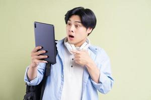 estudiante asiático masculino está apuntando con el dedo a la tableta con una cara de sorpresa foto