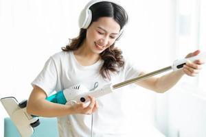 Asian woman listening to music and dancing with a vacuum cleaner photo