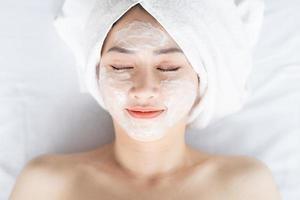 Mujer asiática haciendo tratamientos de belleza, tratamientos de spa y se le aplica crema en la cara foto