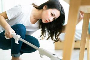 Asian woman cleaning the floor with a vacuum cleaner photo