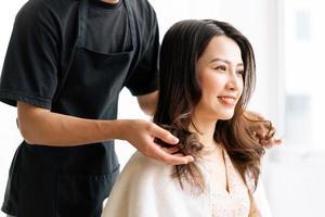 Mujer asiática con expresión feliz haciendo peluquería en salong foto