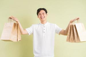 el apuesto hombre asiático sostiene bolsas de papel en la mano foto