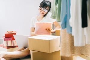 Young Asian businesswoman is sitting on the floor to check her orders from e-commerce sites photo