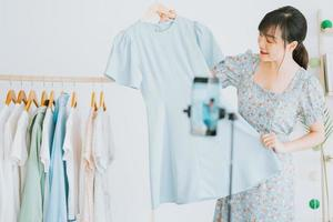 Young Asian beautiful woman is live streaming to sell clothes on social networking platforms and e-commerce sites. This will be the future trend of the ecommerce industry photo