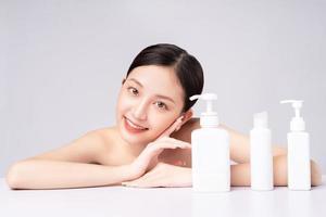 hermosa mujer asiática cuidando su piel con productos naturales foto