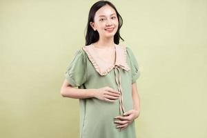Mujer asiática embarazada que se siente feliz y con ganas de dar a luz foto