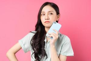 Young Asian woman holding phone in her hand with pensive look photo
