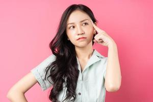Young Asian woman contemplating on a pink background photo