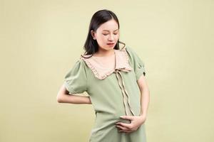 Mujer asiática embarazada que se siente cansada durante el embarazo foto