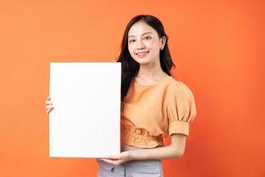 Joven mujer asiática sosteniendo una pizarra blanca sobre fondo naranja foto