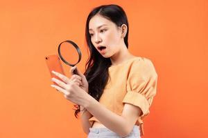 Woman holding a magnifying glass looking at her phone with a surprised expression photo