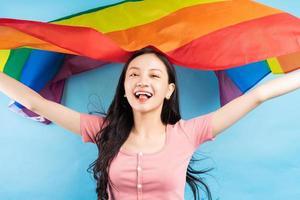 joven asiática sosteniendo la bandera del arco iris para apoyar a la comunidad lgbtq foto