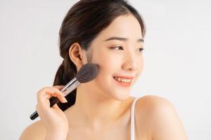 joven asiática sosteniendo un pincel de maquillaje para ella foto