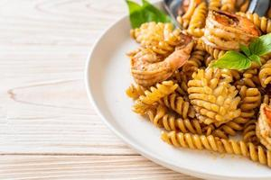 Stir-fried spiral pasta with seafood and basil sauce - fusion food style photo