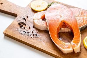 Fresh raw salmon fillet steak with ingredients on board photo