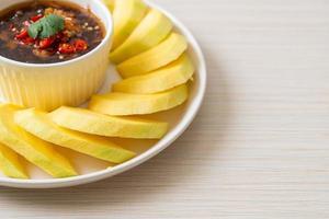 Mango verde y dorado fresco con salsa de pescado dulce - estilo asiático foto