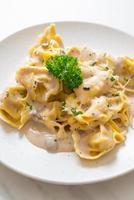 Pasta tortellini con salsa de crema de champiñones y queso - estilo de comida italiana foto