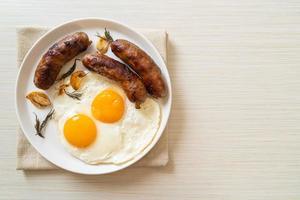 Doble huevo frito casero con salchicha de cerdo frita - para el desayuno foto