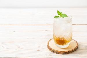 Jugo de ciruela helado con soda y menta en la mesa de madera - bebida refrescante foto