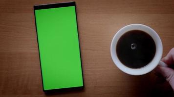 Top view close-up of a male hand putting a cup of coffee near a phone with green screen video