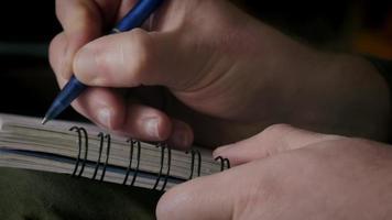close-up van een man die notities schrijft op een notitieboekje video