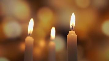 Close-up of three candles burning over a background of colored blurred bokeh video