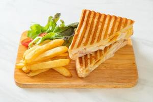 Ham and cheese sandwich with egg and fries photo