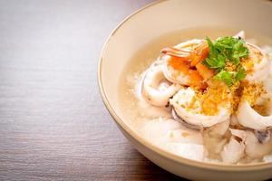 Porridge or boiled rice soup with seafood of shrimp, squid, and fish in a bowl photo