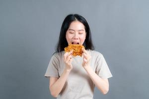 Young Asian woman wearing a sweater with a happy face and enjoy eating fried chicken on grey background photo