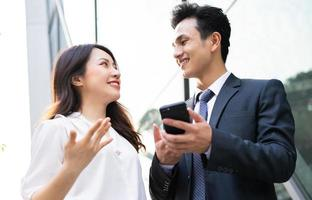 Two Asian business people using smartphone and talking together photo