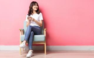 Asian woman sitting on sofa using her phone with a happy expression photo