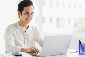 Portrait of male employee working on computer with happy expression photo