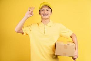 Portrait of a male delivery man holding a cargo box, background photo