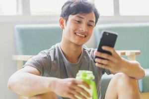 Asian man resting and using phone after exercising photo