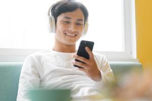 Asian man sitting, enjoying music photo