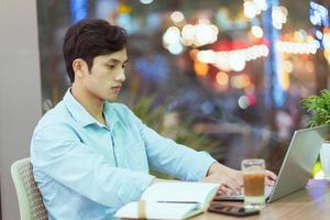 Asian man sitting working alone at a coffee shop photo