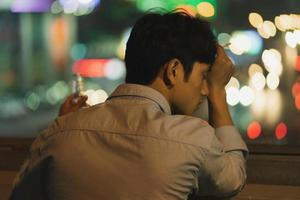 Asian man smoking and drinking in the evening photo