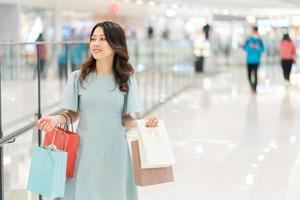 Portrait of young girl holding shopping bag walking in shopping mall photo