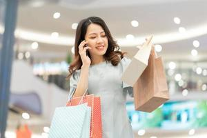 Young girl is shopping and using the phone at the mall photo