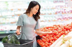 la niña elige comprar verduras en el supermercado foto