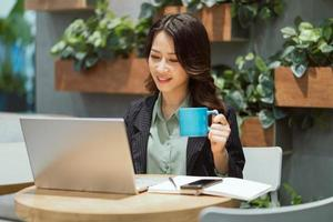 Cheerful young businesswoman working at the coffee shop photo