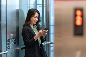 retrato, de, joven, mujer de negocios, posición, en, ascensor, y, utilizar, teléfono foto