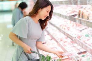 niña está optando por comprar alimentos congelados en el supermercado foto