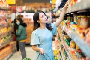 niña está eligiendo comprar productos alimenticios en el supermercado foto