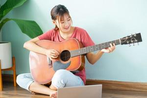 Young Asian woman learning guitar at home photo