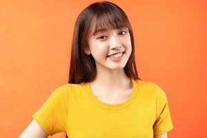 Image of young Asian girl wearing yellow t-shirt on orange background photo
