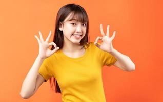 Image of young Asian woman wearing yellow t-shirt on orange background photo
