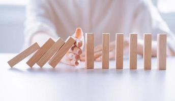 La mano de la mujer detiene el efecto de crisis empresarial de dominó de madera, concepto de protección de riesgos foto