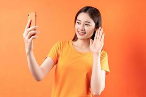 Image of young Asian woman holding smartphone on orange background photo